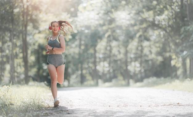スポーツウェアと幸せな公園で屋外を実行しているヘッドセットの若い美しいアジアの女性。