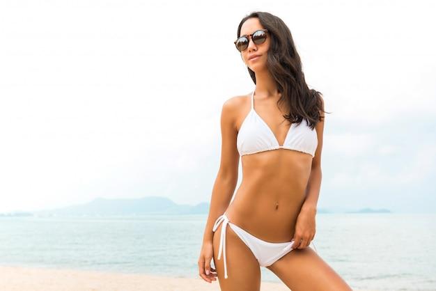 夏のビーチで白いビニキの若い美しいアジア女性
