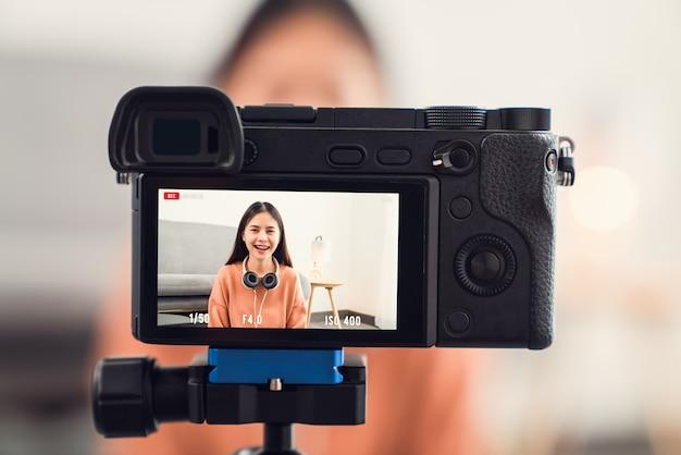 젊은 아름다운 아시아 여성이 라이브 스트리밍 온라인 방송에 대해 이야기하는 동영상 블로거에 영향을 미칩니다.