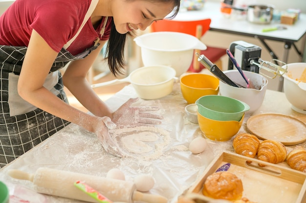 A young beautiful asian woman is baking in her kitchen  , bakery and coffee shop business