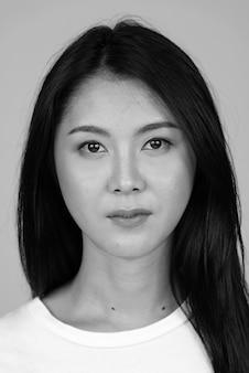 Молодая красивая азиатская женщина изолирована в черно-белом