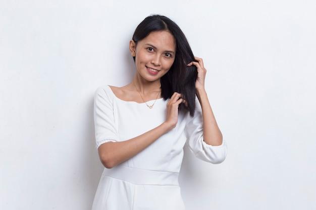 カメラを見て、白の櫛で長い髪をとかす若い美しいアジアの女性