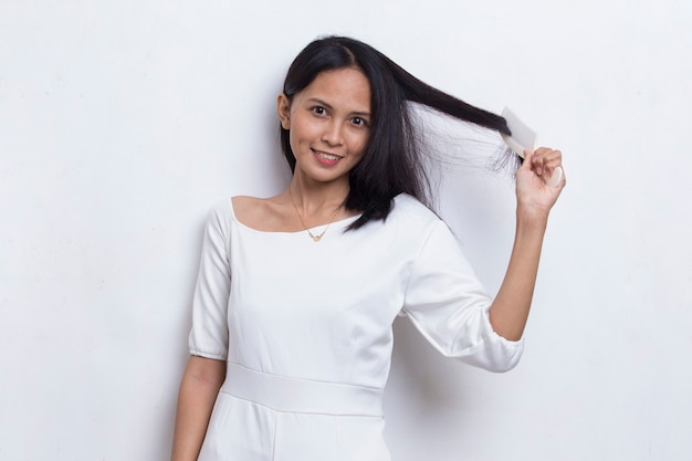 Young beautiful asian woman looking at the camera and combing long hair with a comb  on white