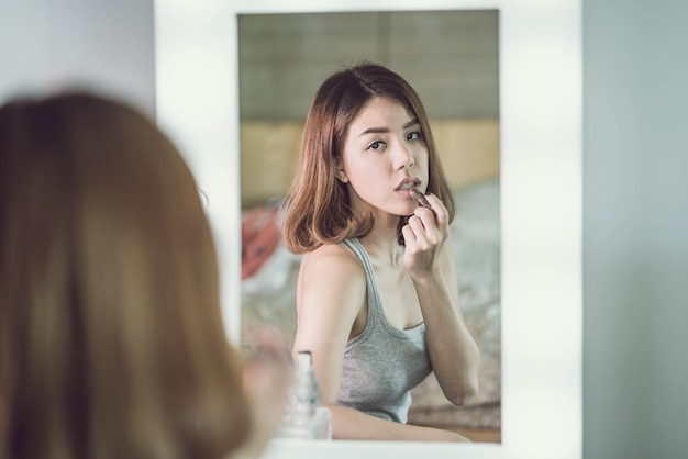 Young beautiful asian woman making make-up near mirror