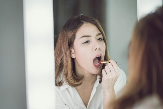 Young beautiful asian woman making make-up near mirror