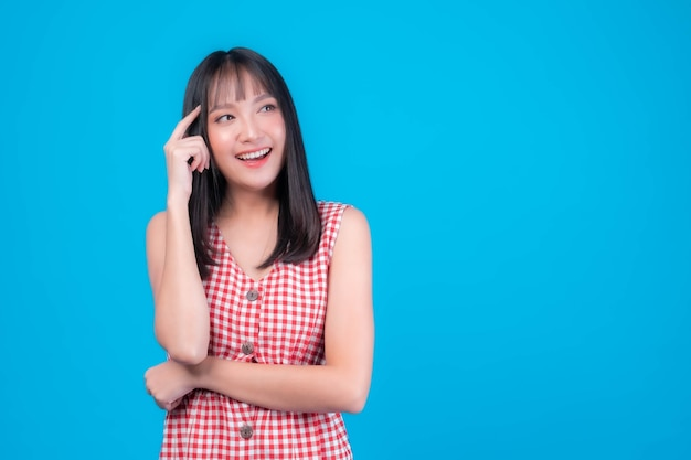 Young beautiful asian woman pointed a finger to her head and smiled isolated on green background ,she think that she is coming up with new plans to get her work done - thinking woman concept