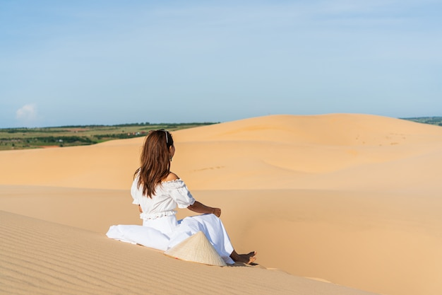 Young beautiful asian woman posing in a white dress in white sand dune desert, muine vietnam.