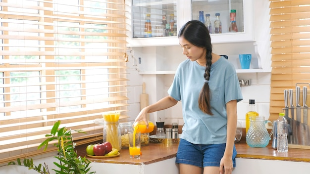 Young beautiful asian woman pouring orange juice on glass while standing in kitchen, asian girl drinking orange juice for healthy, teen woman and healthy lifestyle