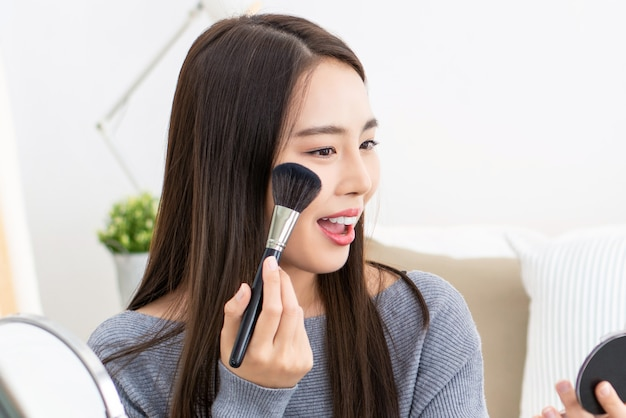 Young beautiful asian woman professional beauty vlogger doing cosmetic makeup tutorial at home