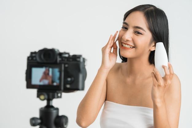 Молодая красивая азиатская женщина, профессиональный влогер красоты или блогер, записывающая макияж, чтобы поделиться в социальных сетях над белой стеной