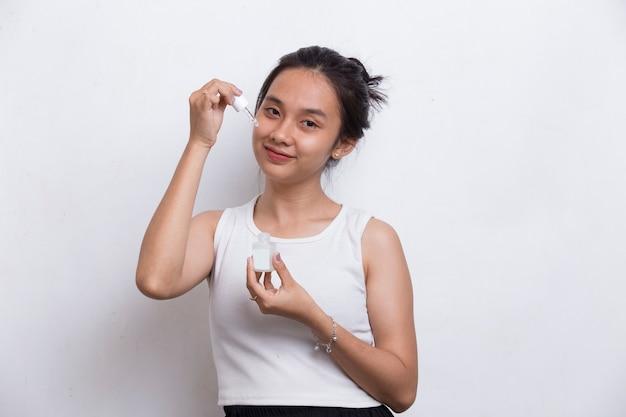 흰색 배경에 격리된 얼굴에 보습 세럼을 바르는 젊은 아름다운 아시아 여성