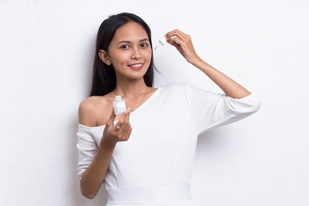 白い背景で隔離の彼女の顔に保湿血清を置く若い美しいアジアの女性