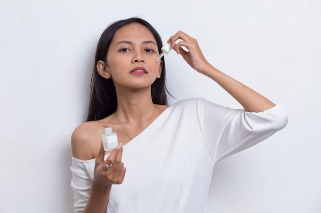 Молодая красивая азиатская женщина наносит увлажняющую сыворотку на лицо на белом фоне