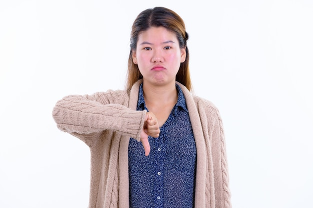 Young beautiful asian woman ready for winter isolated against white wall