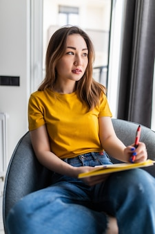 自宅のリビングルームでリラックスし、朝の本を読んで、若い美しいアジアの女性