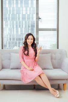 순수한 물 한잔과 함께 소파에서 휴식을 취하는 젊은 아름다운 아시아 여성