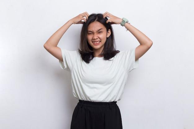 Молодая красивая азиатская женщина почесывает голову рукой, изолированной на белом фоне