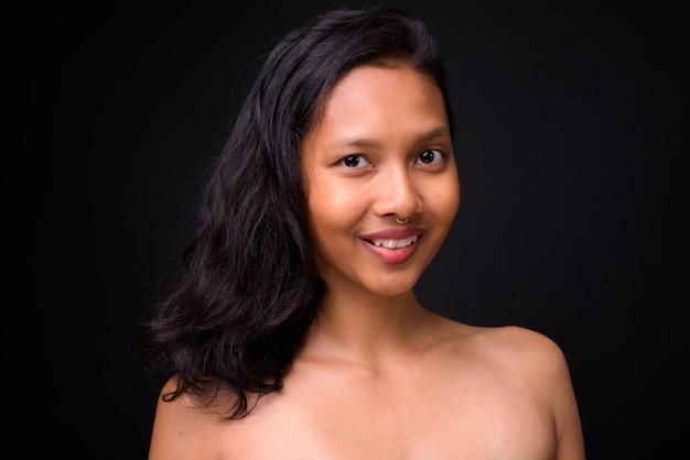 黒い壁に対する健康と美容の概念として上半身裸の若い美しいアジアの女性