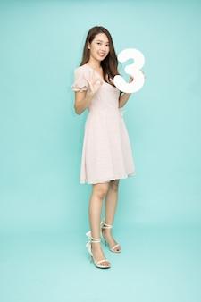 番号3を示し、緑の背景に分離された指番号3で上向きの若い美しいアジアの女性、完全な長さの人々の構成
