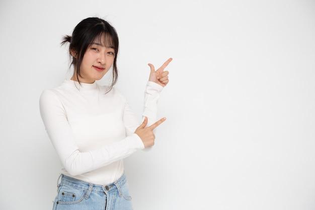 Молодая красивая азиатская женщина улыбается и указывает на пустое пространство для копирования, изолированные на белом фоне