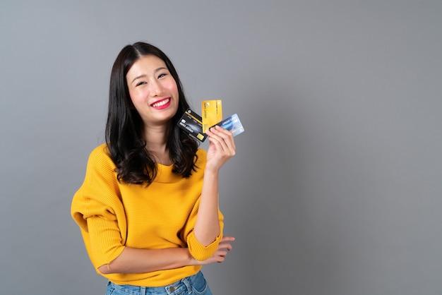 Молодая красивая азиатская женщина улыбается и представляет в руке кредитную карту