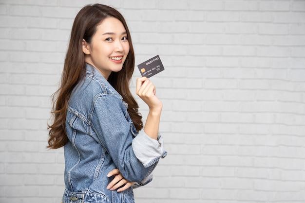 젊고 아름다운 아시아 여성이 웃고, 보여주고, 온라인 비즈니스를 지불하거나 지불하기 위해 신용 카드를 제시하고, 상인에게 지불하거나 상품에 대한 현금 서비스, 카드 소지자 또는 카드를 소유한 사람