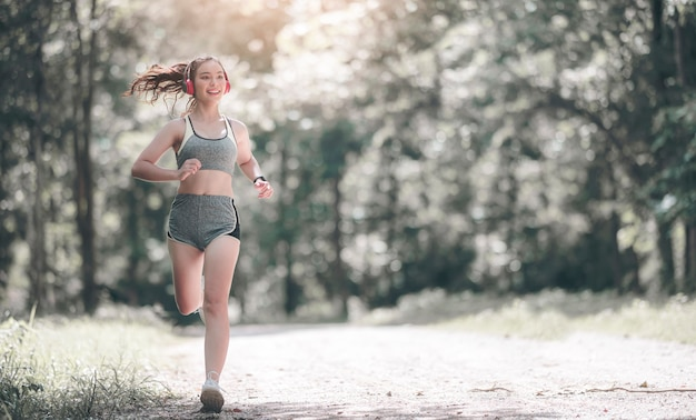 Young beautiful asian woman in sportswear and headset running outdoors in the park with happiness.