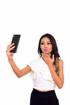 Young beautiful asian woman taking selfie with phone isolated on white