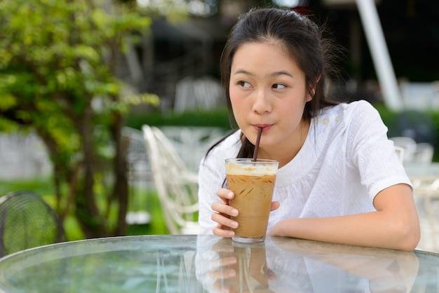 屋外の喫茶店でコーヒーを飲みながら考えている若い美しいアジアの女性