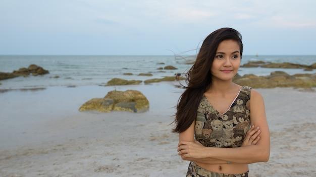 Молодая красивая азиатская женщина думает со скрещенными руками