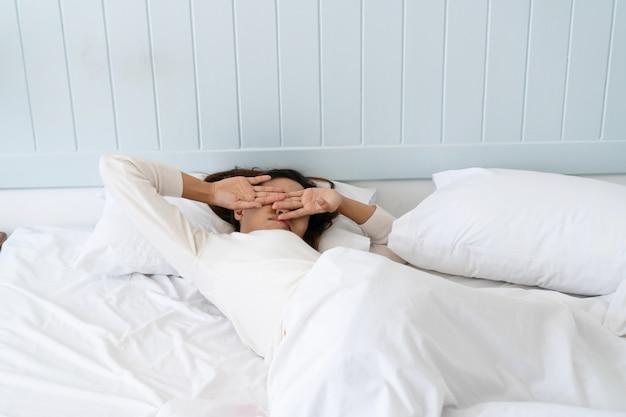 Молодая красивая азиатская женщина слишком ленива, чтобы встать с постели по утрам.