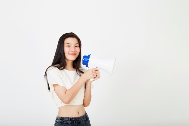 Молодая красивая азиатская женщина в белой рубашке и джинсах держит в руках мегафон, выражая успех и идеи позитивных идей в области маркетинга или продаж