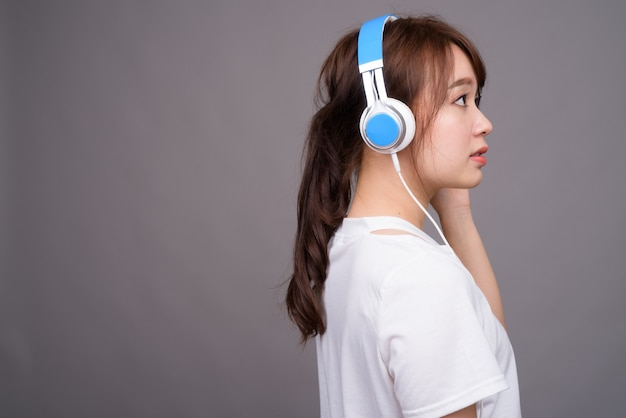 Young beautiful asian woman wearing headphones for music