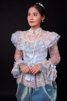 Молодая красивая азиатская женщина в традиционной тайской одежде на черном