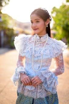 屋外でタイの伝統的な服を着ている若い美しいアジアの女性