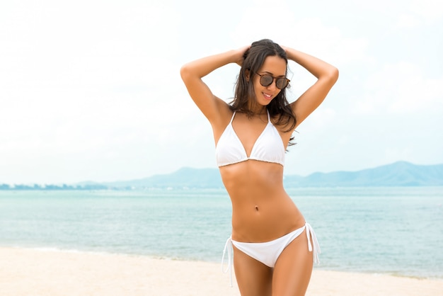 Young beautiful asian woman in white biniki at the beach in summer