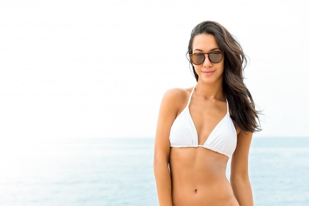 Young beautiful asian woman in white swimsuit at the beach in summer