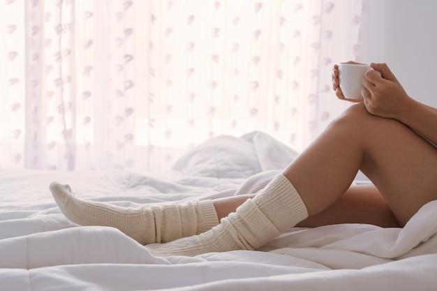 창이 침대에 앉아 커피 한 잔과 젊은 아름 다운 아시아 여자. 복사 공간을 닫습니다. 게으른 하루 개념