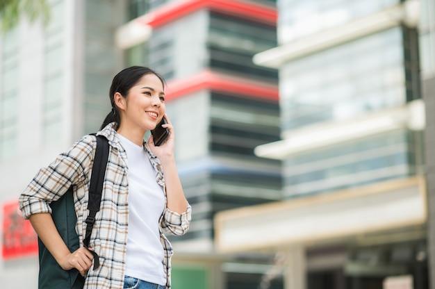スマートフォンを使用してバックパックを持つ若い美しいアジアの女性