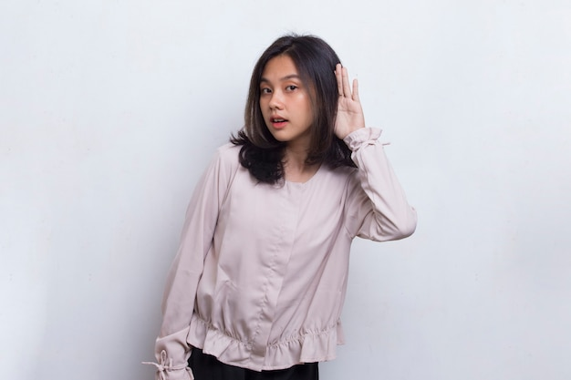 Young beautiful asian woman with hand over ear listening an hearing to gossip  on white background