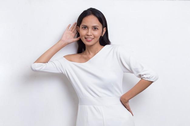 白で隔離のゴシップへのヒアリングを聞いて耳に手渡しの若い美しいアジアの女性