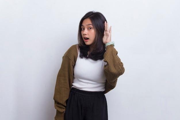 Молодая красивая азиатская женщина с рукой над ухом, слушая слух, чтобы сплетничать на белом фоне