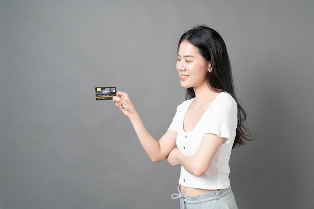 Молодая красивая азиатская женщина со счастливым лицом и представляя кредитную карту в руке, демонстрируя доверие и уверенность в совершении платежа