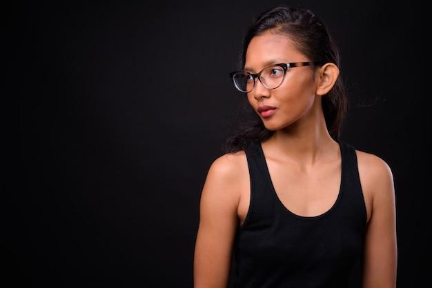 검은 벽에 코 고리와 젊은 아름 다운 아시아 여자
