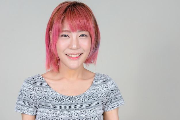 흰 벽에 분홍색 머리를 가진 젊은 아름 다운 아시아 여자