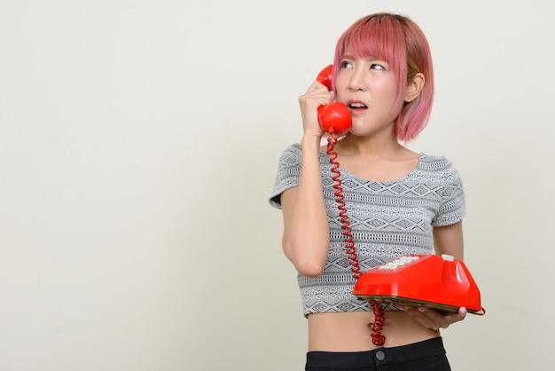 白い壁にピンクの髪を持つ若い美しいアジアの女性