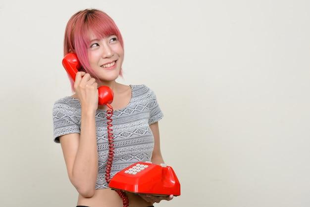 Молодая красивая азиатская женщина с розовыми волосами на белой стене