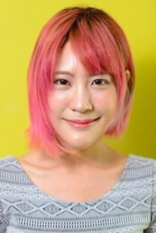 노란색 벽에 분홍색 머리를 가진 젊은 아름 다운 아시아 여자