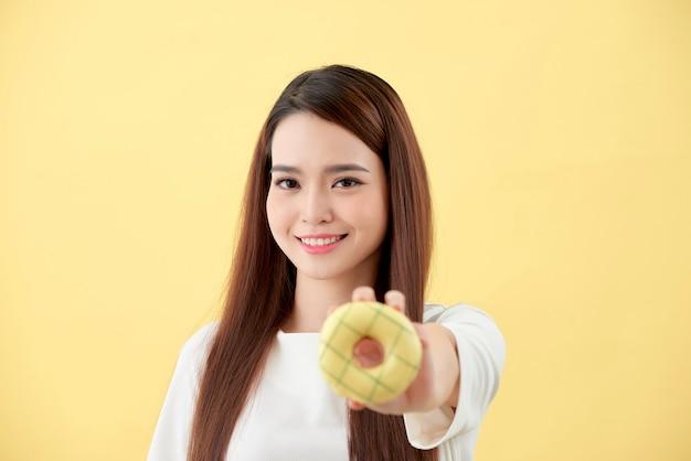 젊고 아름다운 아시아 여성은 흰색 티셔츠를 입고 웃고 쾌활하며 노란색 배경에 격리된 도넛을 들고 있다