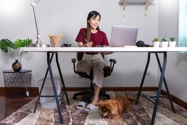 彼女の犬と一緒に家で働く若い美しいアジアの女性